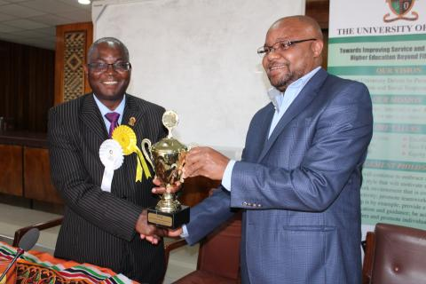 UNZA Vice-Chancellor, Prof. Luke Mumba receives trophies from Acting Deputy Vice-Chancellor, Dr. Jolly Kamwanga during the Trophy Handover ceremony held yesterday, 3 September 2018 in the Senate Chamber