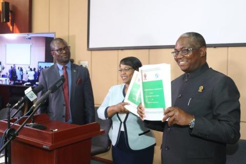 Vice Chancellor Professor Luke E. Mumba and Executive Director Ms Betty S. Bweupe display the Memoranda of Agreement while the Deputy Secretary to Cabinet Dr Martin Mtonga looks on.